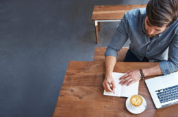 Un homme travaille à une table avec du café, un ordinateur portable, un stylo et du papier.